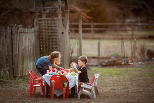 Side view of brother and sister having food at dining table in yardの写真素材 [FYI03685013]