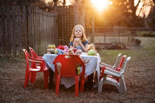 Portrait of girl eating sandwich at yard during sunsetの写真素材 [FYI03685014]