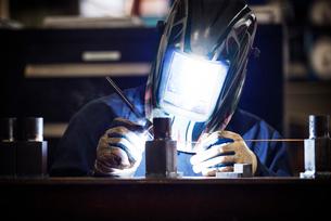 Worker working on metal in factoryの写真素材 [FYI03685514]