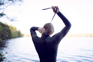 Rear view of female swimmer wearing wetsuit at lakeshoreの写真素材 [FYI03685577]