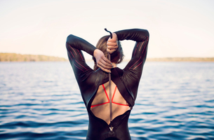 Rear view of swimmer wearing wetsuit at lakeshoreの写真素材 [FYI03685584]
