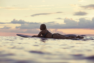 Side view of sensuous woman lying on surfboard in sea against sky during sunsetの写真素材 [FYI03685817]