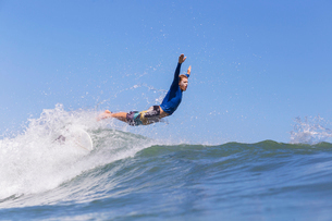 Side view of male surfer jumping on sea against clear blue skyの写真素材 [FYI03685832]
