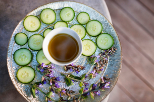 High angle view of cucumber slices and liquid in plate at health spaの写真素材 [FYI03685989]