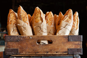 Bread loaves in wooden container at bakeryの写真素材 [FYI03686071]