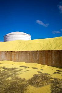 Storage tank by heap of sand at factory against blue skyの写真素材 [FYI03686133]