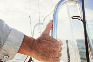Cropped image of hand holding metal on boat at seaの写真素材 [FYI03686339]