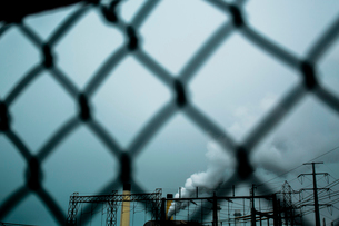 Smoke emitting from factory seen through chainlink fence against skyの写真素材 [FYI03686360]