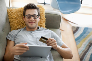 Smiling man shopping online on tablet while lying on sofa at homeの写真素材 [FYI03686478]