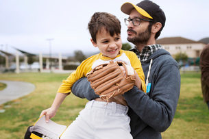 Father carrying happy son while standing on sports fieldの写真素材 [FYI03686581]