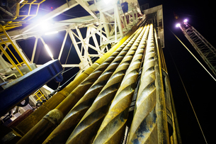 Low angle view of metallic machinery in oil rig against sky at nightの写真素材 [FYI03686808]