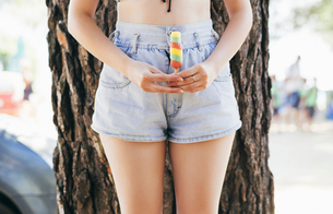 Midsection of seductive woman holding ice lolly while standing against tree trunkの写真素材 [FYI03686842]