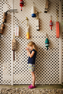 Side view of curious girl looking into cupped hands while standing by buoys hanging on partitionの写真素材 [FYI03687063]