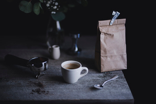 Espresso cup with paper bag and portafilter on wooden tableの写真素材 [FYI03687244]