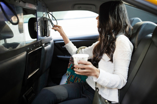Young woman holding disposable glass while making contactless payment through smart phone in taxiの写真素材 [FYI03687729]