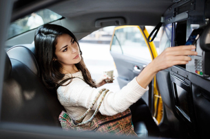 Young woman making contactless payment through smart phone in taxiの写真素材 [FYI03687731]