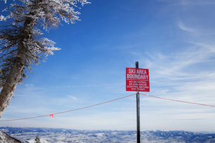 Low angle view of warning sign against sky during winterの写真素材 [FYI03687788]