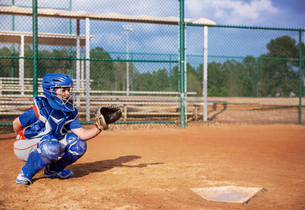 Baseball catcher crouching on fieldの写真素材 [FYI03688453]