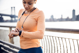 Female runner checking the time while standing on footpath with Williamsburg Bridge in backgroundの写真素材 [FYI03688525]