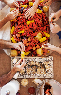 Overhead view of people eating a crayfish boil with potatoes, corns and oysters at dining tableの写真素材 [FYI03688686]