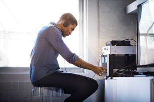 Side view of man listening music at homeの写真素材 [FYI03688932]