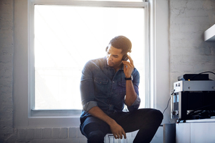 Man listening music through headphones at homeの写真素材 [FYI03688935]