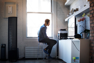 Side view of man listening music while sitting by window at homeの写真素材 [FYI03688937]