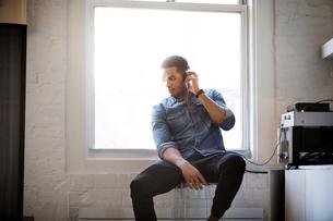 Man listening music through headphones at homeの写真素材 [FYI03688939]