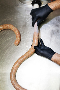 Overhead view of chef making sausage in commercial kitchenの写真素材 [FYI03689261]