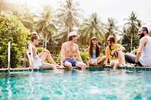 Cheerful friends spending leisure time at poolsideの写真素材 [FYI03689374]