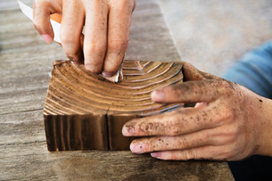 Cropped image of carpenter carving wood in workshopの写真素材 [FYI03689408]