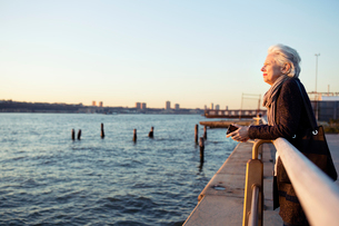 Side view of senior woman leaning on railing by seaの写真素材 [FYI03689475]