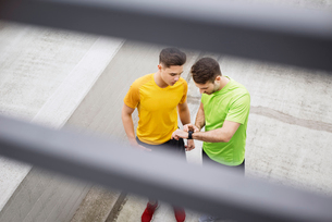High angle view of male athletes checking the time on footpath at parking lotの写真素材 [FYI03689660]