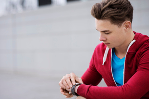 Male athlete checking the time outdoorsの写真素材 [FYI03689666]