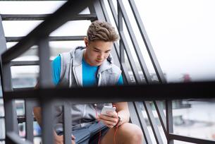 Male athlete using smart phone on metallic stepsの写真素材 [FYI03689676]