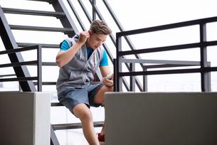 Male athlete listening music through smart phone on metallic stepsの写真素材 [FYI03689678]