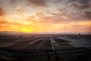 Airport runway against cloudy sky during sunsetの写真素材 [FYI03689867]