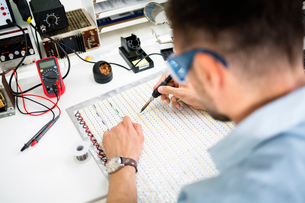 High angle view of engineer soldering circuit at table in electronics industryの写真素材 [FYI03689934]