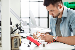 Concentrated engineer soldering circuit at table in electronics industryの写真素材 [FYI03689941]