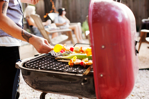 Midsection of man barbecuing in yardの写真素材 [FYI03690085]