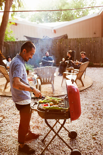 Man barbecuing while friends sitting in yardの写真素材 [FYI03690086]