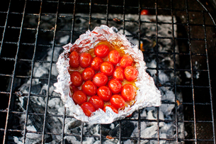 Overhead view of cherry tomatoes in foil on barbecue grillの写真素材 [FYI03690103]