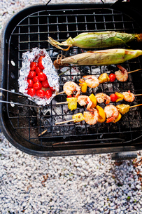 Overhead view of cherry tomatoes with prawns in skewers and corns on barbecue grillの写真素材 [FYI03690105]