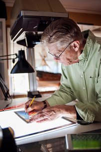 Senior man drawing on graphics tablet at homeの写真素材 [FYI03690396]