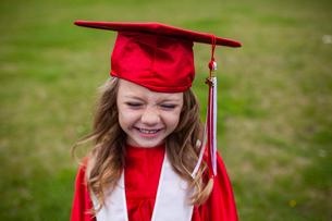 Happy girl in graduation gown on fieldの写真素材 [FYI03690492]