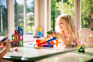Girl playing with building blocks at homeの写真素材 [FYI03690656]