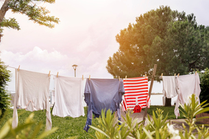 Clothes drying on clothesline at field against skyの写真素材 [FYI03690728]