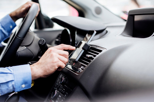 Cropped image of businessman using GPS on smart phone in carの写真素材 [FYI03690760]