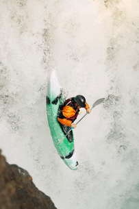 High angle view of whitewater kayaker descending waterfallの写真素材 [FYI03691336]