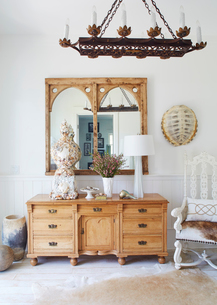 Chandelier over cabinet and mirrors in beach cottageの写真素材 [FYI03691742]